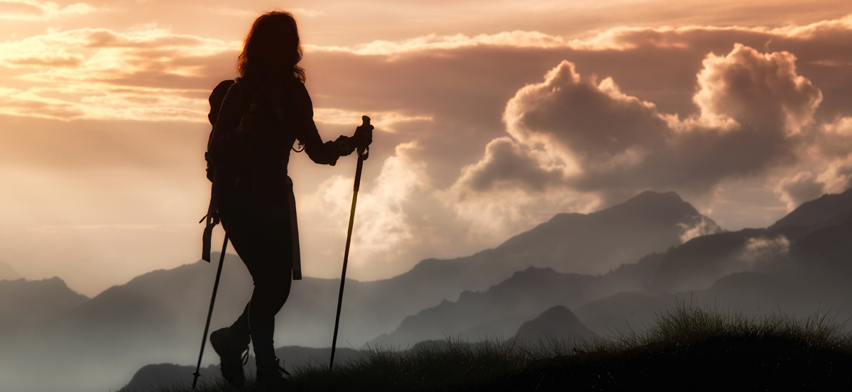 Frau wandert auf den Bergen mit Blick in die Ferne - Freiheitsgefühl